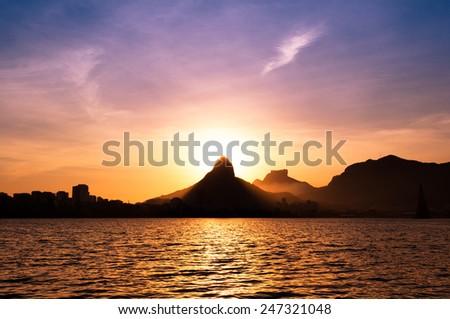 Beautiful View of Rio de Janeiro Sunset Behind Mountains at Rodrigo de Freitas Lake - stock photo