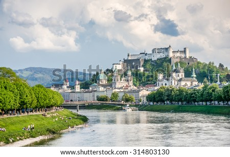 Beautiful view of Salzburg skyline with Festung Hohensalzburg and Salzach river in summer with dramatic cloudscape, Salzburg, Salzburger Land, Austria - stock photo