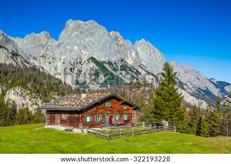 Beautiful view of scenic mountain landscape in the Alps with traditional mountain chalet and fresh green meadows on a sunny day with blue sky in fall - stock photo