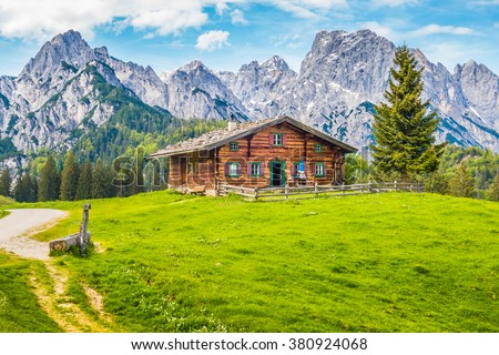 Beautiful view of scenic mountain landscape in the Alps with traditional old mountain chalet and fresh green meadows on a sunny day with blue sky and clouds in spring - stock photo