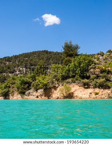 Beautiful view of St. Croix lake in Verdon and the forested hills of the coastline. (Provence, France) Sunlight on the water surface. - stock photo