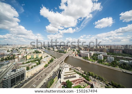 Beautiful view of the cityscape with modern buildings, river, blue sky and clouds.