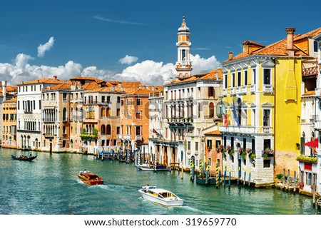Beautiful view of the Grand Canal with boats and colorful facades of old medieval houses from the Rialto Bridge in Venice, Italy. Venice is a popular tourist destination of Europe. - stock photo