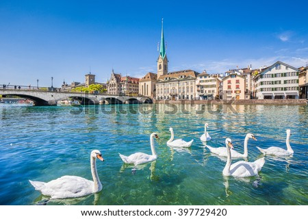 Beautiful view of the historic city center of Zurich with famous Fraumunster Church and swans on river Limmat on a sunny day with blue sky, Canton of Zurich, Switzerland - stock photo