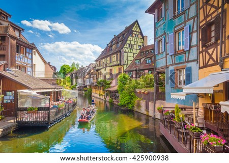 Beautiful view of the historic town of Colmar, also known as Little Venice, with tourists taking a boat ride along traditional colorful houses on idyllic river Lauch in summer, Colmar, Alsace, France - stock photo