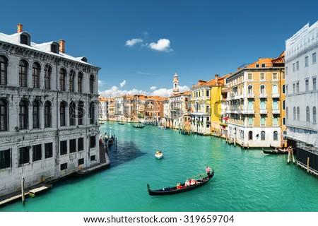 Beautiful view of the Palazzo dei Camerlenghi (Fondamenta de la Preson) and the Grand Canal with gondolas from the Rialto Bridge in Venice, Italy. Venice is a popular tourist destination of Europe. - stock photo