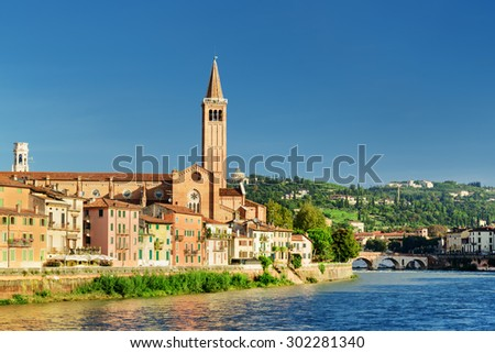 Beautiful view of the Santa Anastasia church, colorful facades of old houses on waterfront of the Adige River and the Ponte Pietra in Verona, Italy. Verona is a popular tourist destination of Europe. - stock photo
