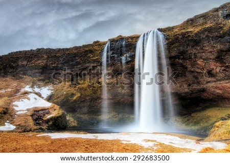 Beautiful view of the Seljalandsfoss waterfall in Iceland with ominous clouds in winter