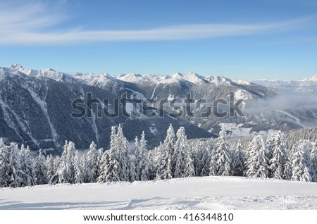 Beautiful view of the snow-covered spruces, mountains and low clouds in winter - stock photo