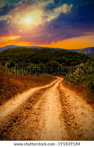 beautiful view of the sunset in a field on a rural road. Vintage style - stock photo