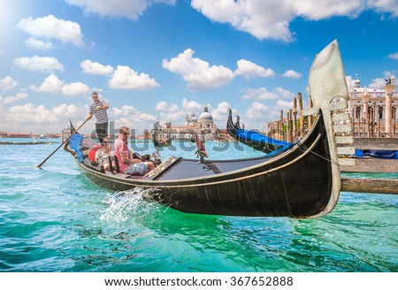 Beautiful view of traditional Gondola on Canal Grande near Piazza San Marco with historic Basilica di Santa Maria della Salute in the background on a sunny day with blue sky and clouds, Venice, Italy - stock photo