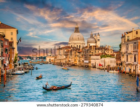 Beautiful view of traditional Gondola on famous Canal Grande with Basilica di Santa Maria della Salute in golden evening light at sunset in Venice, Italy - stock photo