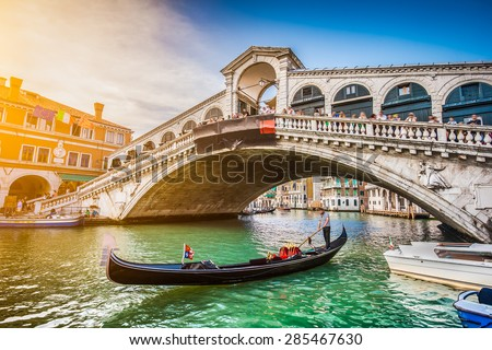 Beautiful view of traditional Gondola on famous Canal Grande with Rialto Bridge at sunset in Venice, Italy with retro vintage Instagram style filter and lens flare effect - stock photo