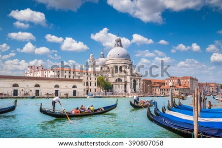 Beautiful view of traditional Gondolas on famous romantic Canal Grande with historic Basilica di Santa Maria della Salute in the background on a sunny day with blue sky and clouds in Venice, Italy - stock photo