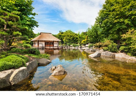 Beautiful view of traditional Japanese Garden with tea house and pond - stock photo