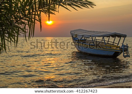 Beautiful view on moored boat on waves against of sunset at sea. Lake Victoria, Tanzania