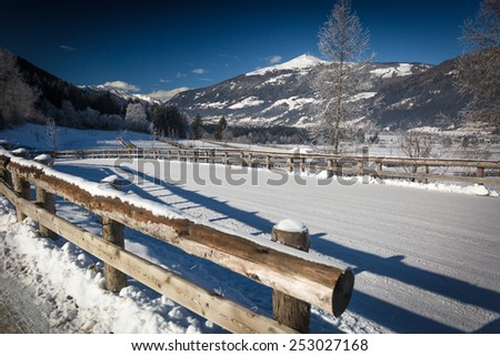 Beautiful view on mountain road covered by snow in Austrian Alps at sunny day - stock photo