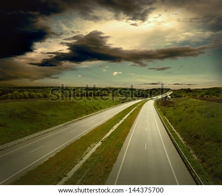 Beautiful view on the road under sky with clouds - stock photo