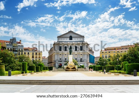 Beautiful view on the Royal Theatre (Teatro Real) from the Plaza de Oriente on the blue sky background with white clouds in Madrid, Spain. Madrid is a popular tourist destination of Europe. - stock photo