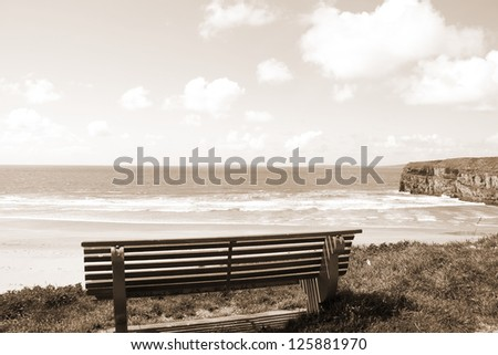 Beautiful view over the Ballybunion beach and cliffs in Ireland from a wooden bench in sepia - stock photo