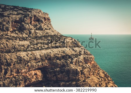 Beautiful view to the rocks and oir rig out at sea near the Gozo Island, Malta