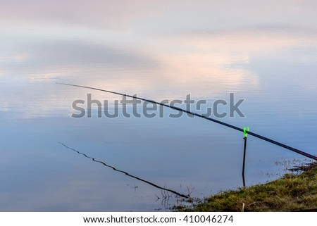 Beautiful view with a fishing rod and reflections of sky and clouds in the river in the light of the setting sun