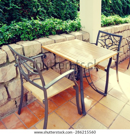 Beautiful view with table and chairs at a open terrace cafe in the garden, Portugal. Square toned image, instagram effect - stock photo