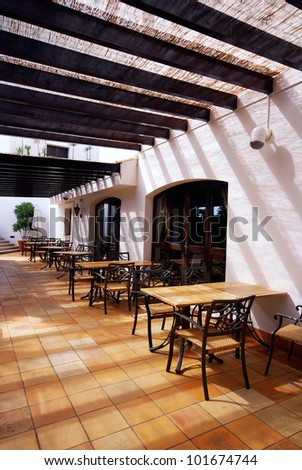 Beautiful view with tables and chairs at a open terrace cafe in mediterranean town (Portugal) - stock photo