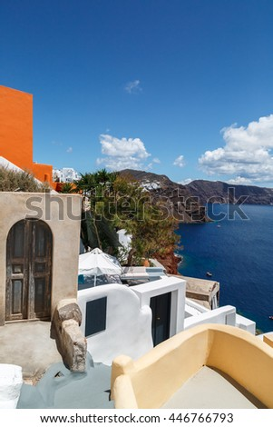 Beautiful view with white buildings, blue doors and roofs, the village of Oia at the Island Santorini, Greece