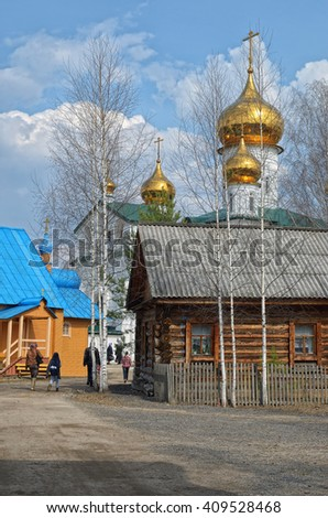 Beautiful views of the Orthodox monastery with Golden domes of the churches against the blue, cloudy sky. - stock photo