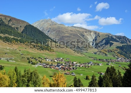 Beautiful Village Surrounded by Rolling Green Hills and Blue Sky