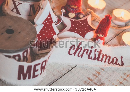 Beautiful vintage christmas ribbons and toys on the wooden table. Cute and pleasant decorations in rustic style - stock photo