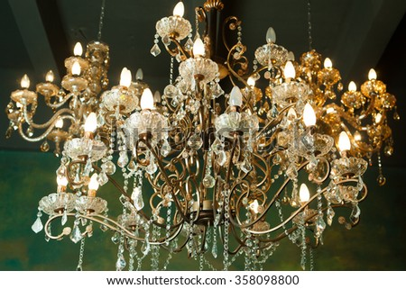 Beautiful vintage crystal chandelier in a room, Golden tones.