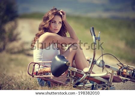 beautiful vintage girl sitting next to bike, summer time - stock photo