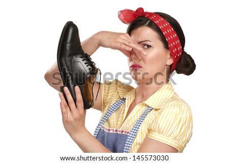 beautiful vintage housekeeper holding  a smelly shoes with facial expression on white - stock photo