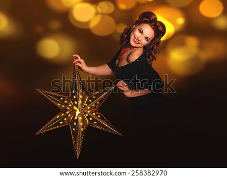 Beautiful vintage pin-up girl holding shining lightning metal star in her hands on dark background with copy space - stock photo