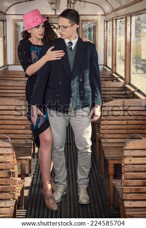 Beautiful vintage style couple inside retro train coach have an argument and disagreements, fashion vintage style
