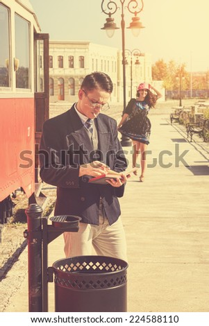 Beautiful vintage style couple outside retro train coach have a romantic encounter while he reading  book and she race toward him smiling , fashion vintage style - stock photo