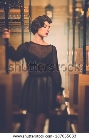 Beautiful vintage style young woman inside retro train coach