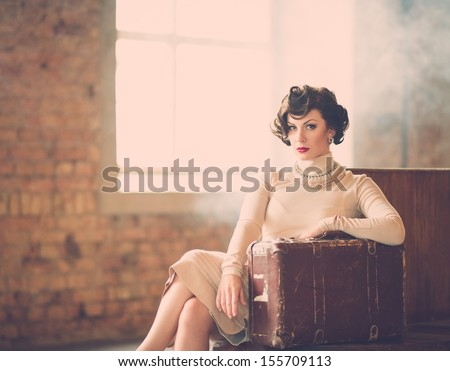 Beautiful vintage style young woman with suitcase on a train station