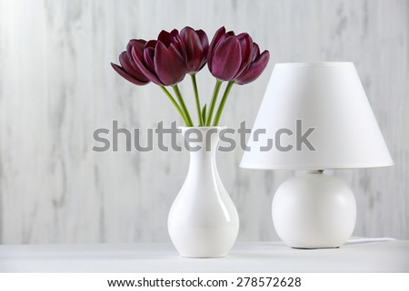 Beautiful violet tulip in vase with lamp on gray background - stock photo