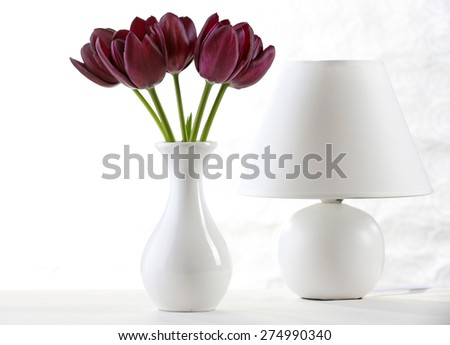 Beautiful violet tulip in vase with lamp on light background - stock photo