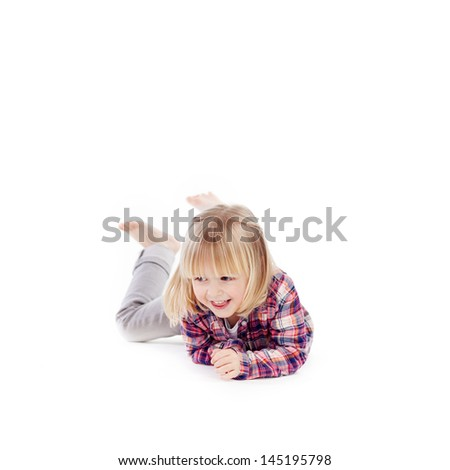 Beautiful vivacious little blond girl romping on the floor lying on her stomach kicking her bare feet in the air - stock photo