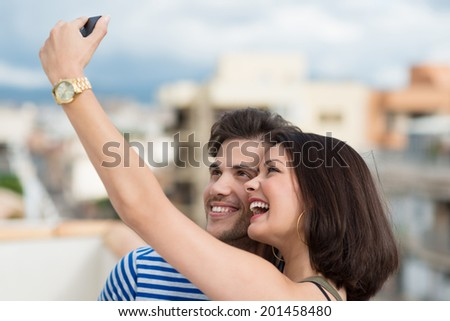 Beautiful vivacious young couple taking a self portrait on their mobile phone posing close together laughing at the camera - stock photo