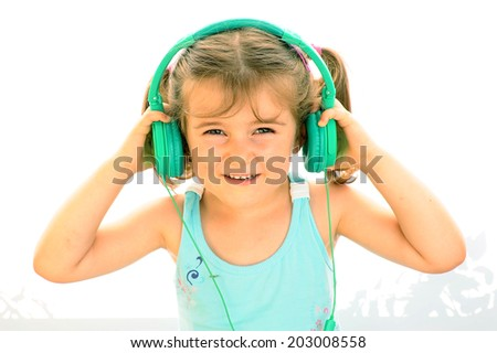 Beautiful vivacious young woman listening to music as she sits - stock photo