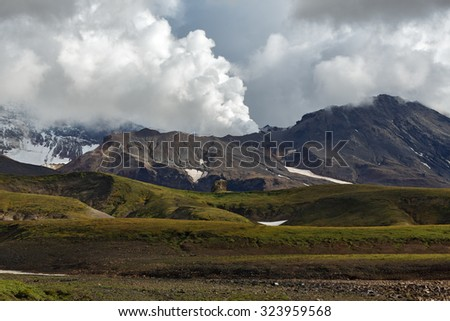 Beautiful volcanic landscape of Kamchatka Peninsula: picturesque view of active Mutnovsky Volcano, fumarolic activity of volcano - steam and gas emissions from crater. Kamchatka, Far East, Russia. - stock photo
