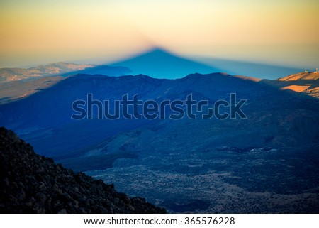 Beautiful volcanic landscape with big volcano shadow in national park of Teide on Tenerife island. Top view on the sunset - stock photo