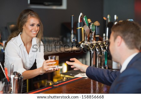 Beautiful waitress serving handsome businessman in a classy bar - stock photo