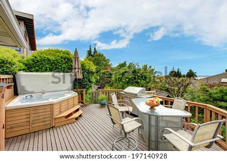 Beautiful walkout deck with jacuzzi , patio table set and barbecue - stock photo