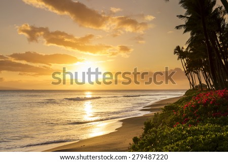 Beautiful, warm tropical sunset on the white sands of Kaanapali Beach in Maui, Hawaii. A fabulous destination for vacation and travel. - stock photo